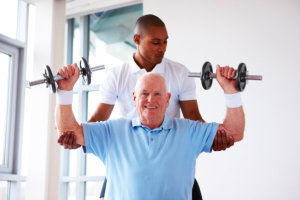 caregiver and old man doing physical therapy